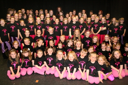 dance school pupils in show costume of black tee shirt with logo and pink leggings